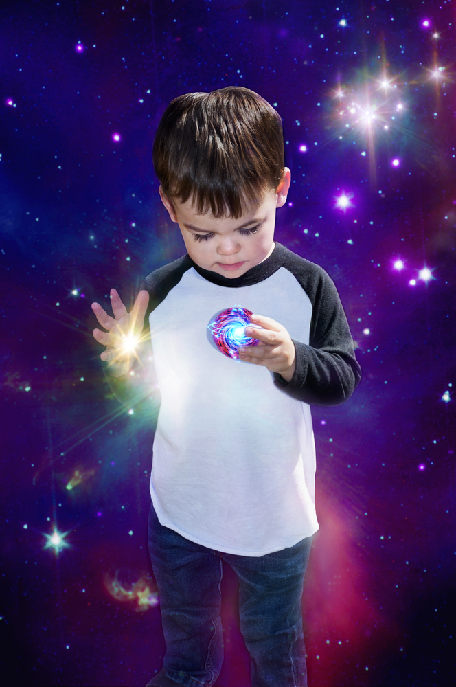 Signs you have a psychic child image of little boy child's imagination in space holding planet and light shining through hand