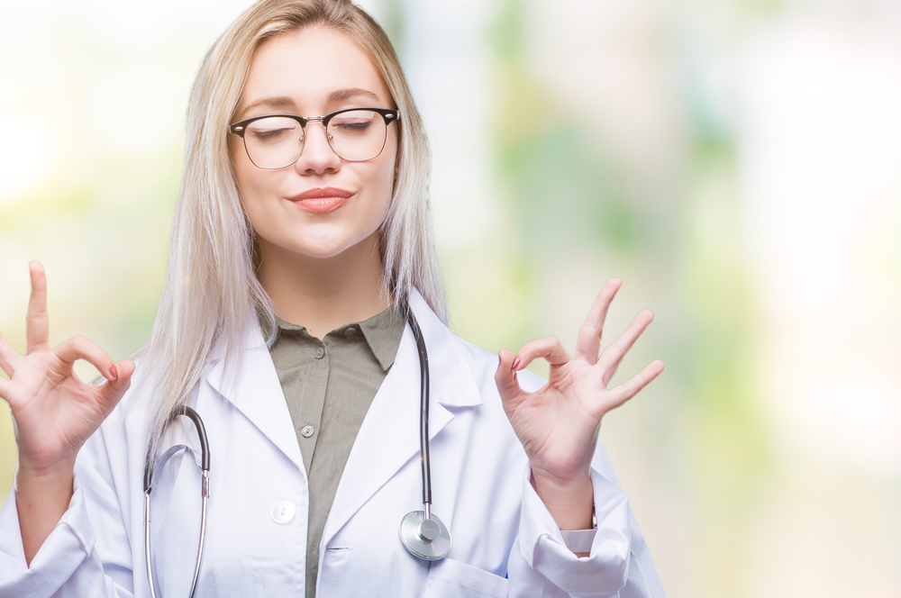 Young blonde doctor woman over isolated background relax and smiling with eyes closed doing meditation gesture with fingers. Yoga concept.